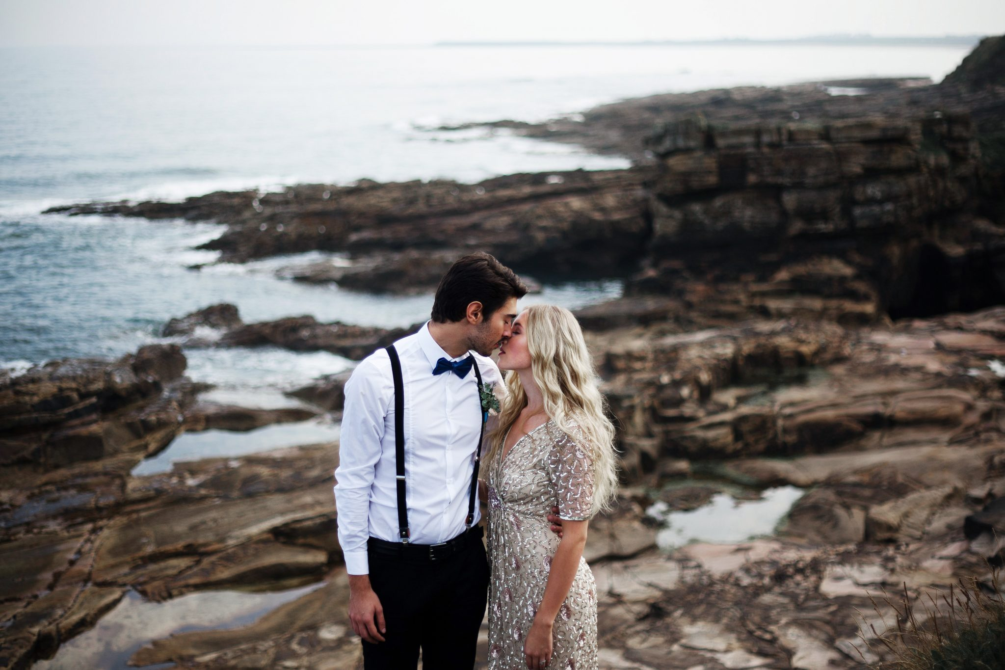 Bride and Groom on cliffs at summer beach wedding in northumberland