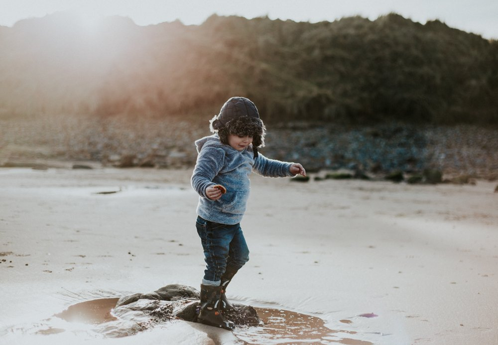 Toddler plays jumping in rock pools at Amble Beach Family Photo Session