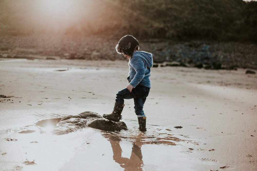 toddler playing in rock pools at Amble Beach Family Photo Session