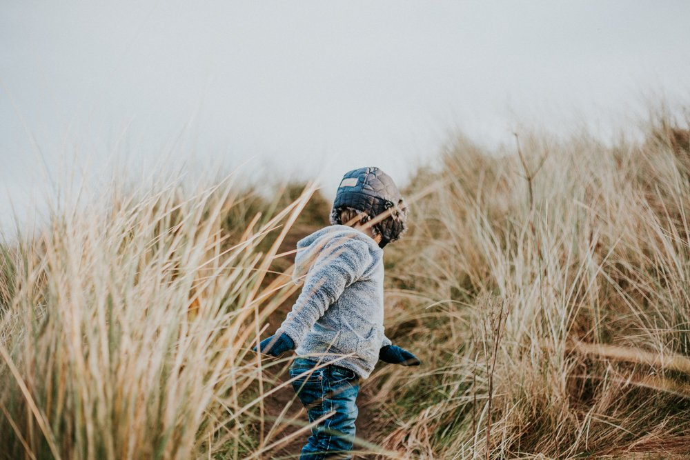 Little boy playing hide and seek in the dunes at amble beach family photo session