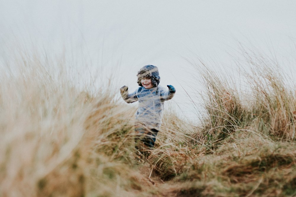 Little boy running through the long grass on the sandy dunes in northumberland at amble beach family photo session