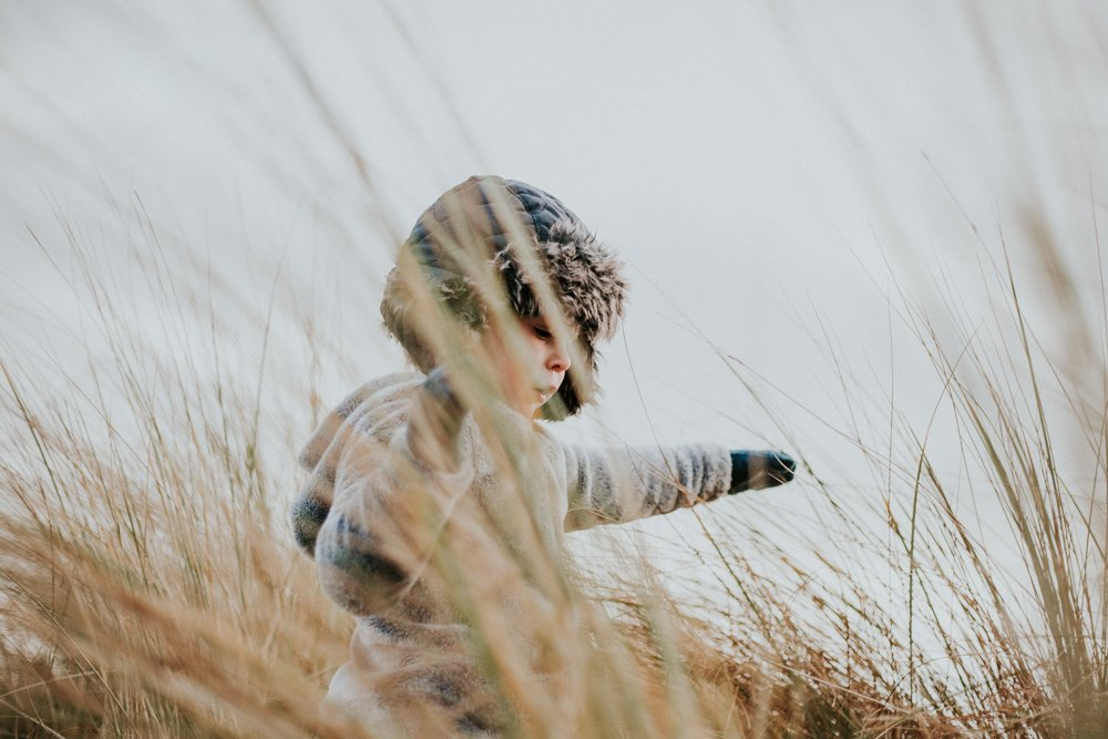creative photograph of little boy playing in the dunes on amble beach
