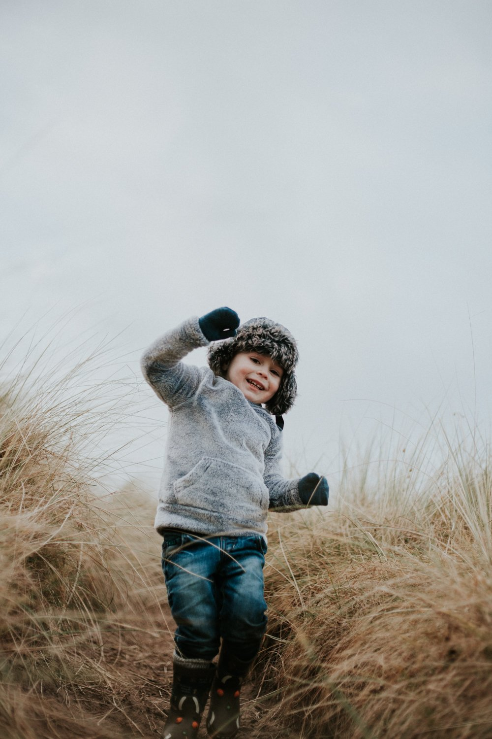 little boy Jumping though the long grass dunes at Amble Beach Family Photo Session