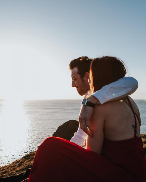 Couple embrace on top of cliffs at sunset elopement - wedding photographer north east