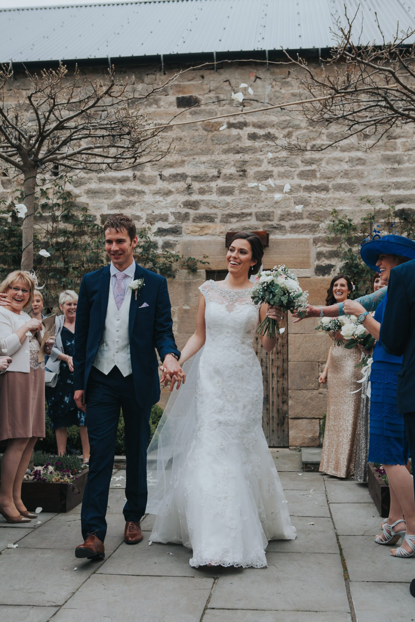 Healey Barn Wedding - Bride and groom walk out to confetti