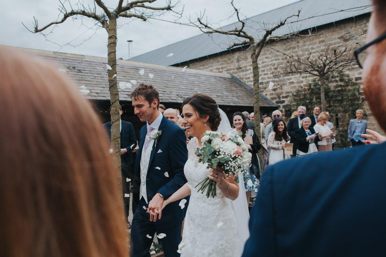 Healey Barn Wedding - Bride and Groom walk out to confetti