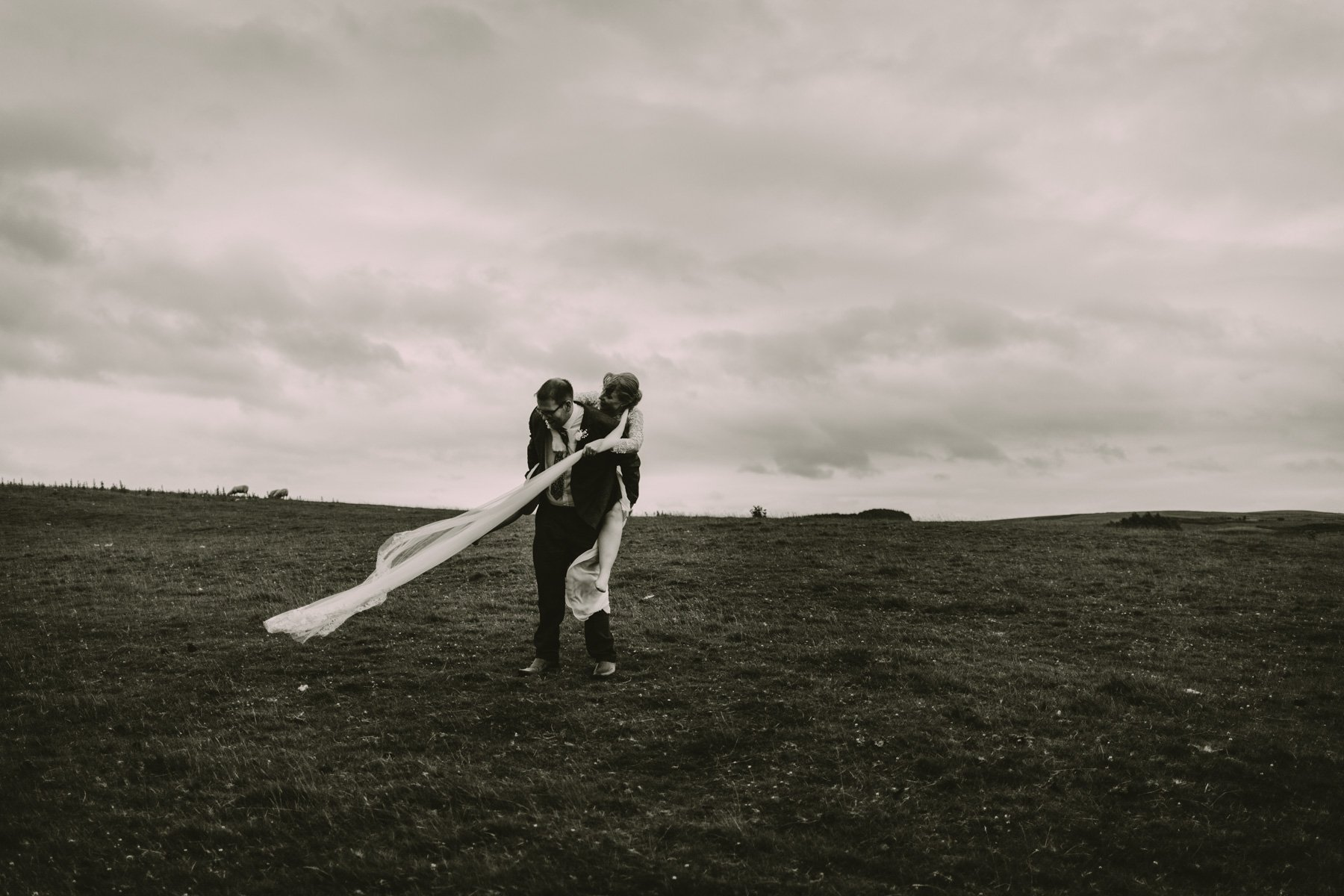 North East Wedding Photographers - Bride and groom portraits piggy back in field
