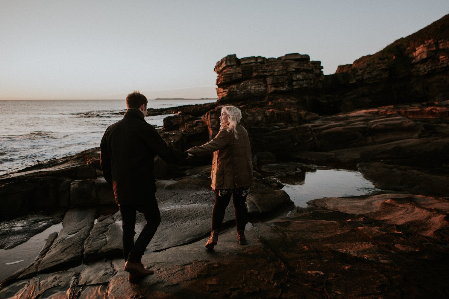couple walking along cliffs at engagement shoot - north east wedding photographer