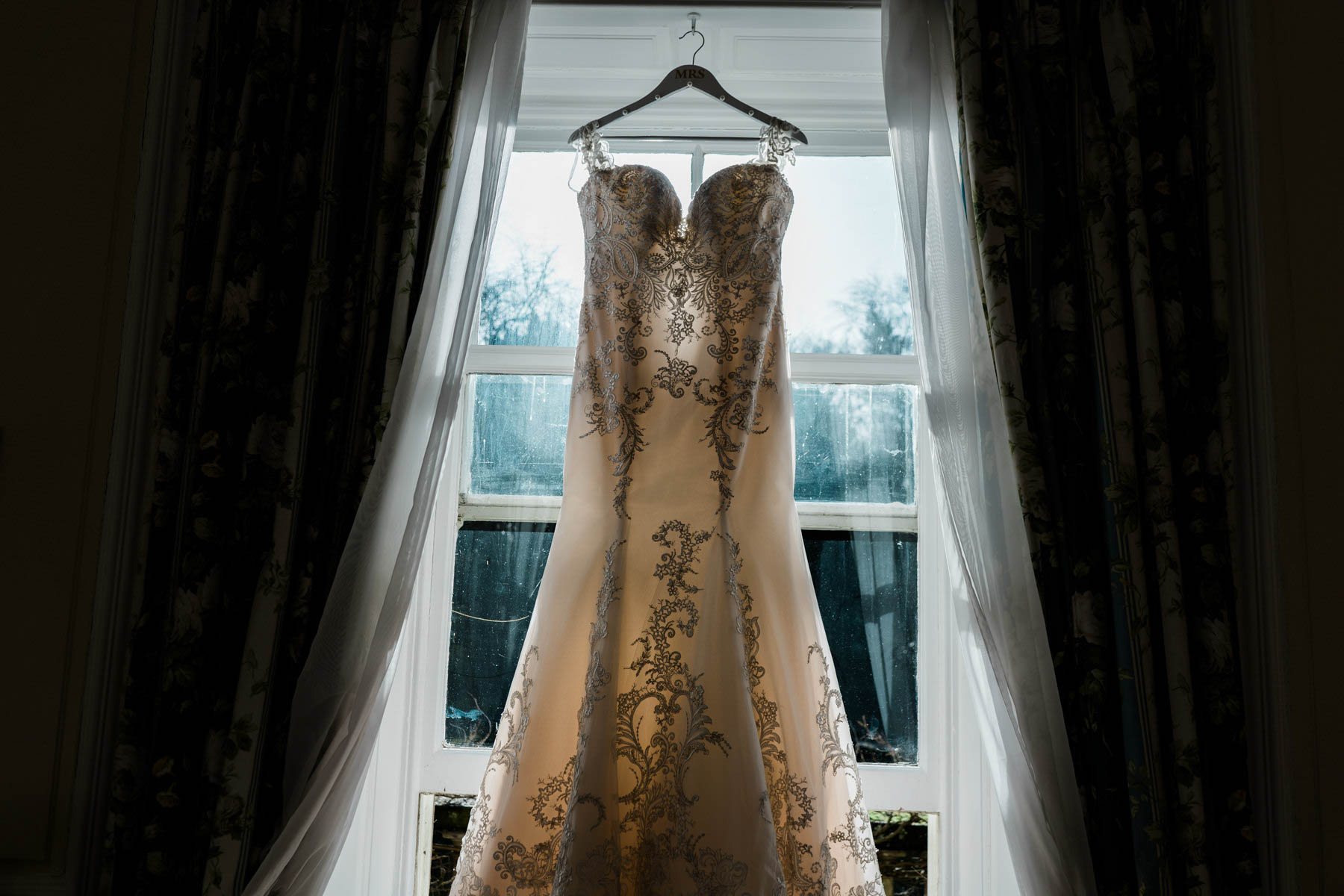 Eshott Hall Wedding Photographer | wedding dress hanging in window